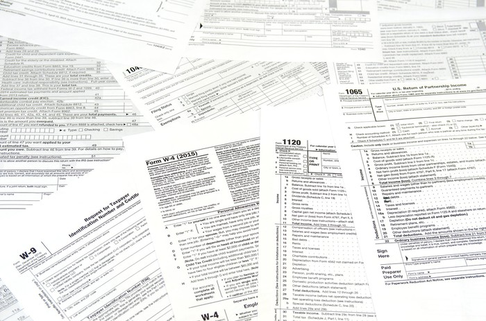 Various IRS tax forms and instructions laid out across a flat surface.