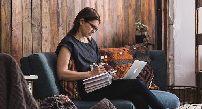 Female entreprenuer working at home on couch with laptop and paper notebook.