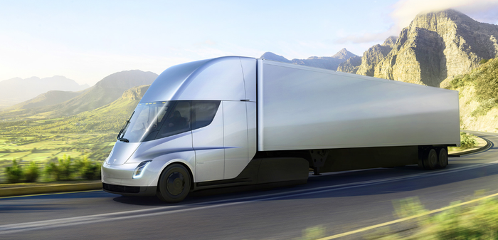 Tesla Semi traveling on a rural road with mountains in background.