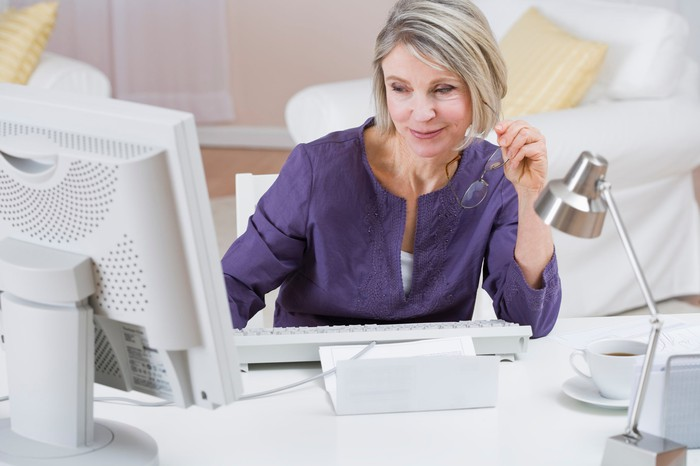 Woman looking at the screen of a desktop computer.