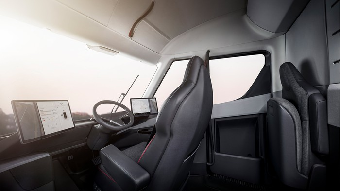 The interior of Tesla Semi, featuring a center-positioned driver's seat and two touchscreen displays.