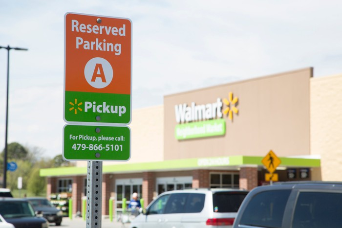A reserved parking for online grocery pickup sign at a Walmart store.