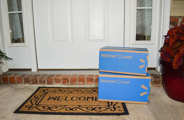 Two Wal-Mart boxes stacked in front of a door.