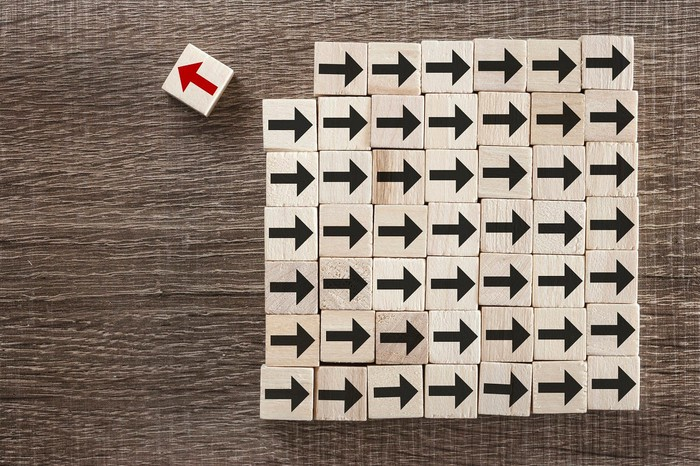 A square of blocks with arrows on them. All the arrows except one are black and point to the right. One is red and points to the left.