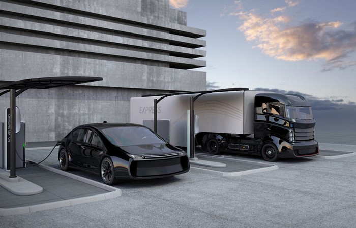 An electric car and electric heavy truck plugged in for charging.