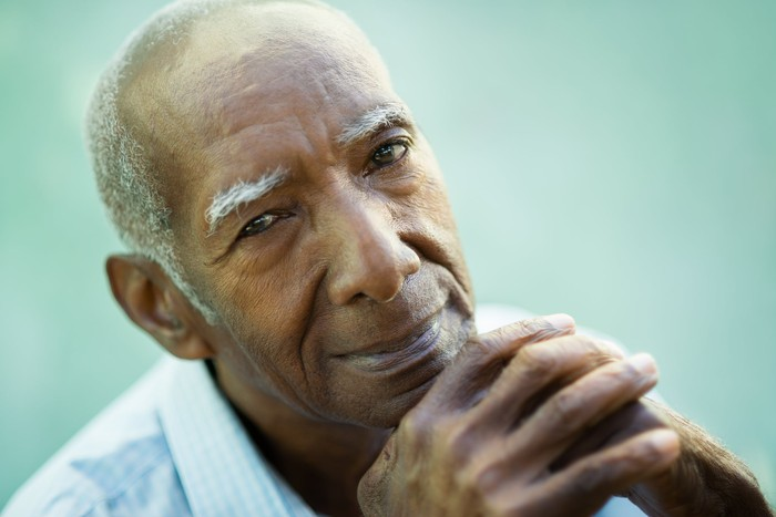 A smiling elderly man resting his chin on his interlocked hands.