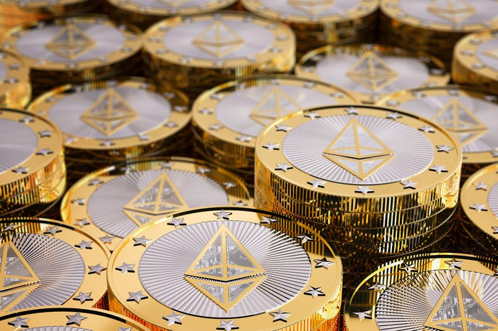 Numerous shiny gold/silver coins with Ethereum symbol on them.