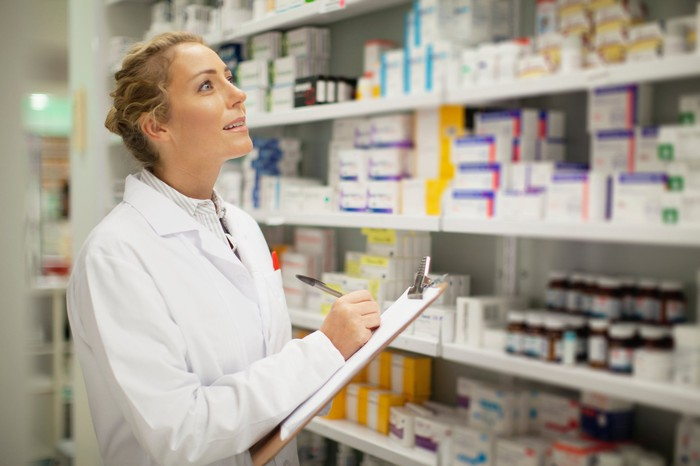 A pharmacist writing on a clipboard as she looks up at shelves of pills.