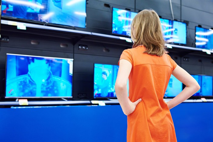 Woman standing in front of TVs in a store.