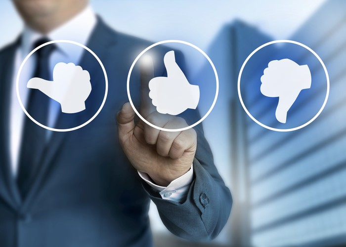 A businessman in a suit points at a thumbs up icon floating in front of him.