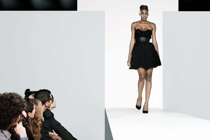 Model in low-cut, short, tight black dress with flouncy skirt on fashion show runway