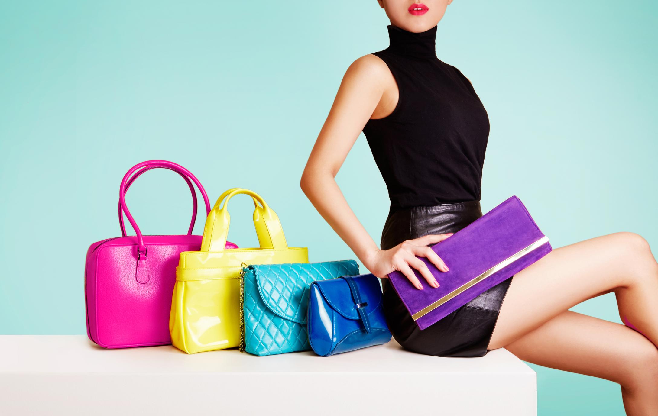Woman wearing short, tight black dress seated beside colorful handbags