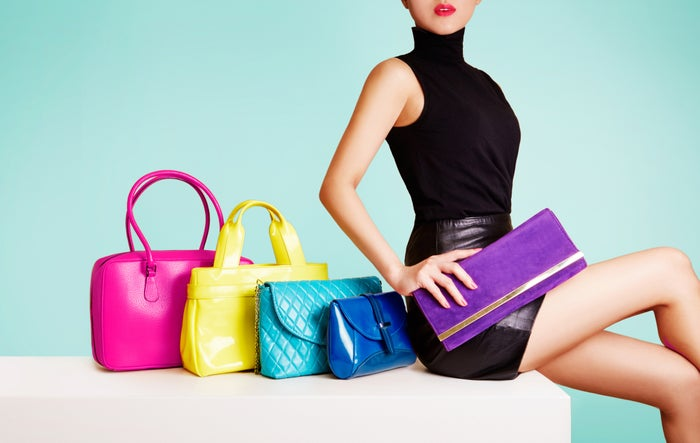 Woman wearing short, tight black dress seated beside colorful handbags