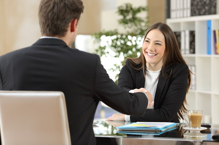 Businesswoman shakes hands with a businessman while sitting at a desk.