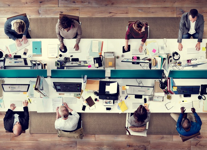 Eight businesspeople sit at work spaces along a table.