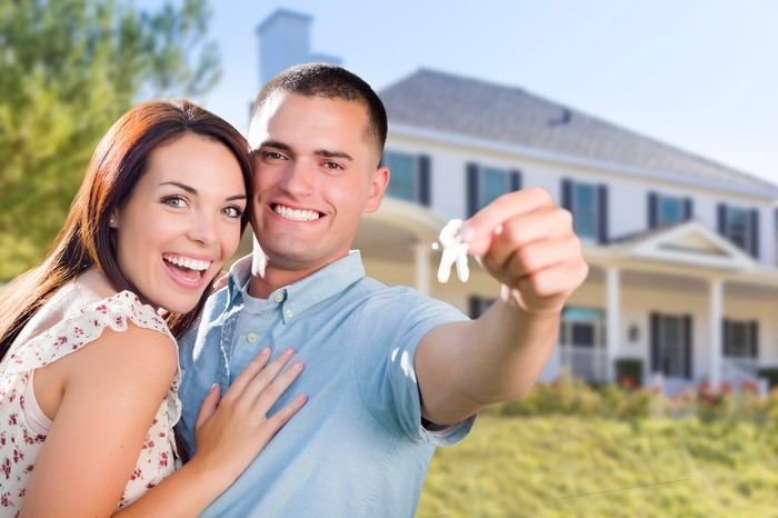 A couple showing keys to their new house