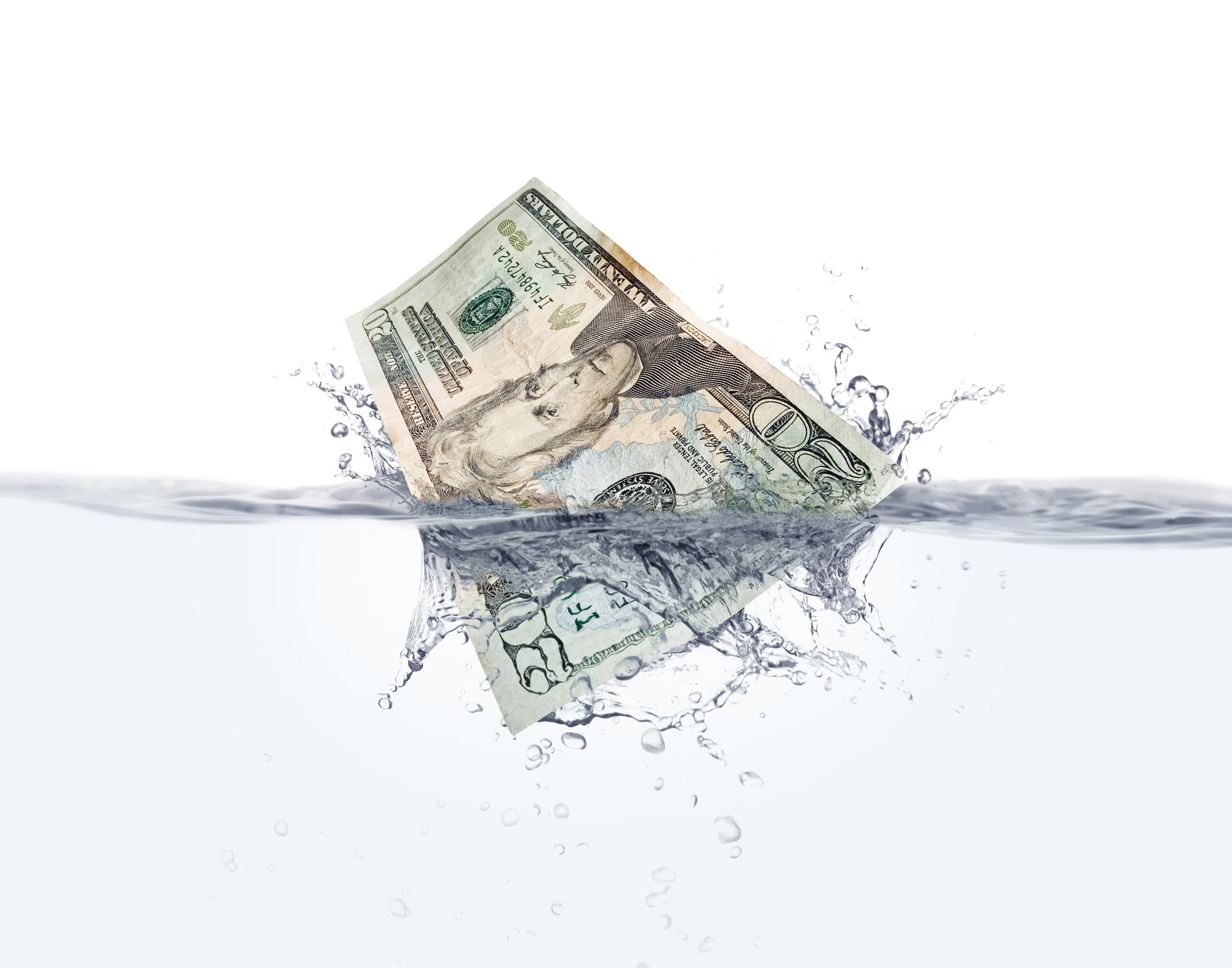 A twenty dollar bill splashing into the water.