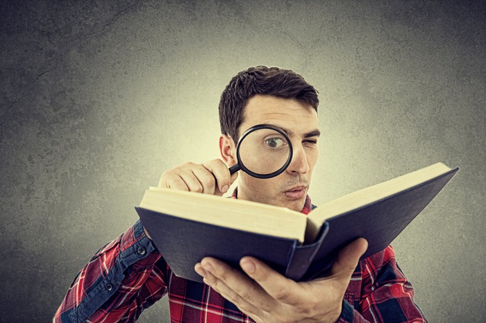 Man reading a book with a magnifying glass.