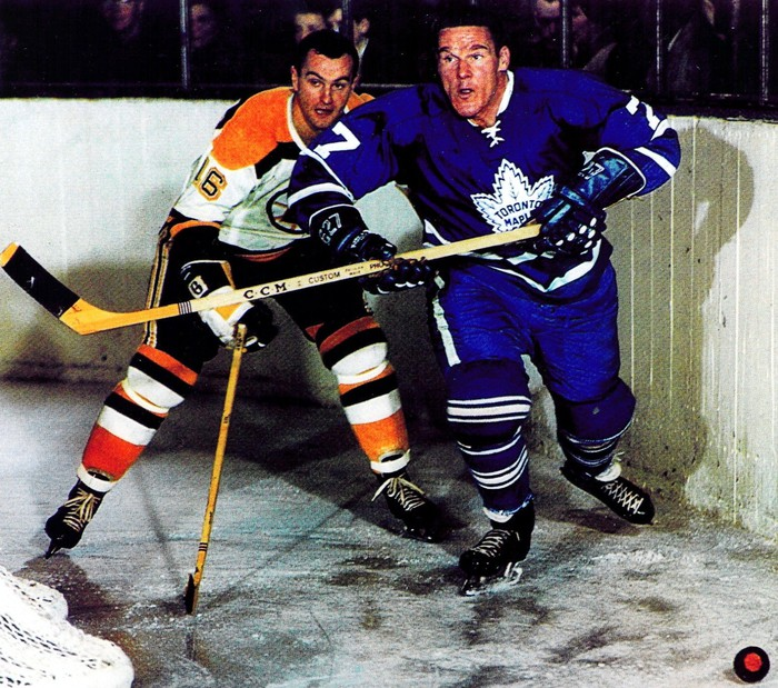 Tim Horton fights for the puck against an opponent.
