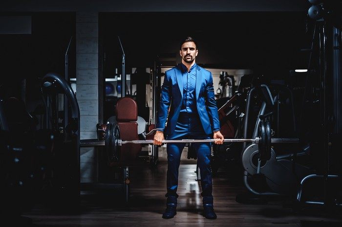 A man in a business suit lifts a barbell in a gym.