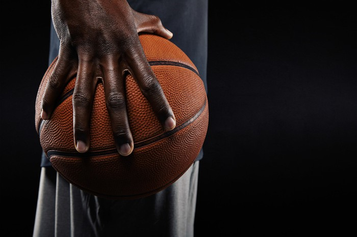 side shot of man holding basketball in one hand