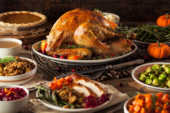 A roasted turkey surrounded by plenty of side dishes and pumpkin pie.