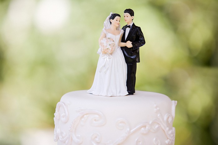 Bride and groom figurines on top of a wedding cake.