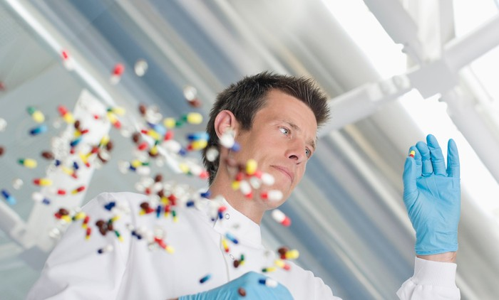 Pharmacist examining a colored tablet, with a scattering of about 50 pills on a clear glass table.