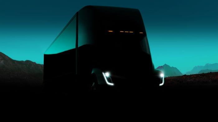 Tesla Semi driving down a road at night.