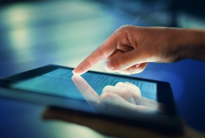 A hand touches an LCD screen on a tablet.