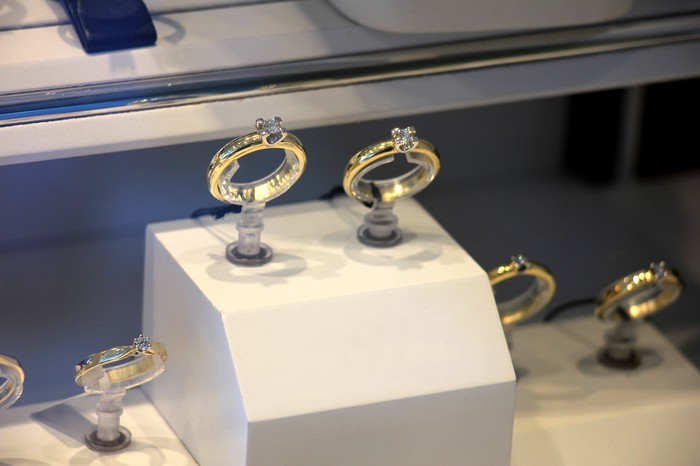 Two engagement rings in a glass case inside a jewelry store.