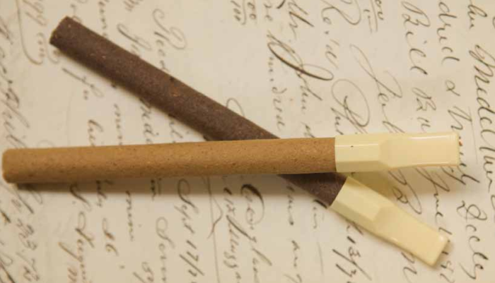 Two old-style cigarettes with filters on top of a piece of paper with old-style handwriting.