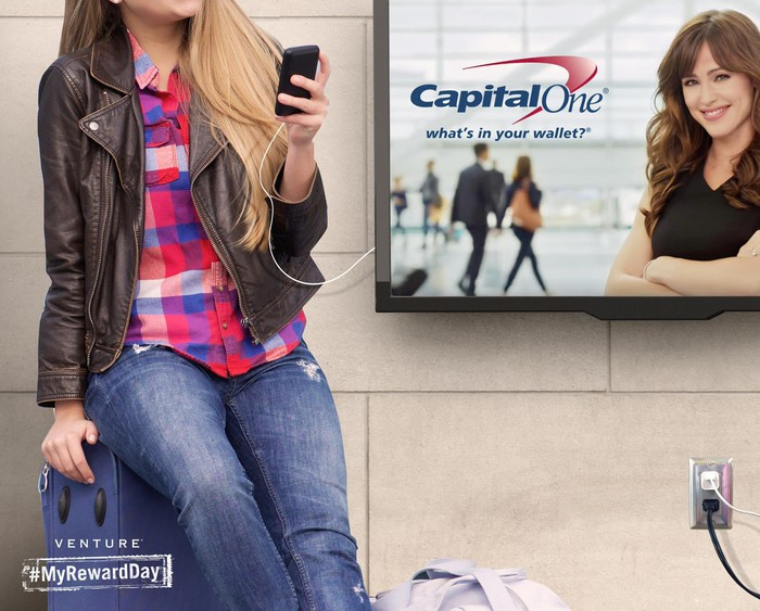 Person charging phone next to Capital One ad in an airport
