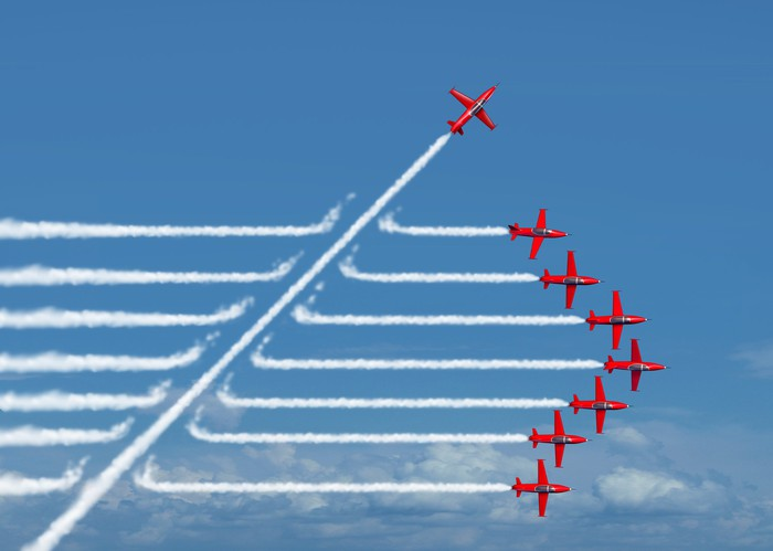 Seven red jets flying in a tight V formation as another red jet cuts diagonally across their white contrails, headed upward
