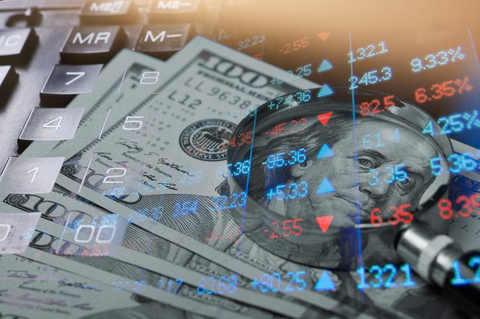 U.S. $100 bills and stock-market quotes superimposed over a calculator.