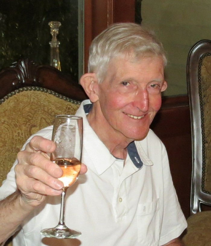 Man (Hayford Peirce) smiling at camera, toasting with a champagne glass. He is wearing a white polo with a white undershirt, sitting in a chair at a table, in front of what appears to be a candle holder in a case.