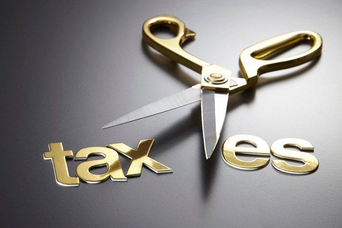 """A pair of scissors cutting through the word """"taxes."""""""