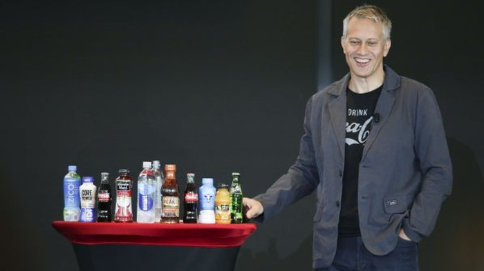 Coca-Cola CEO James Quincey standing beside an array of Coca-Cola products at the company's 2017 investor conference.