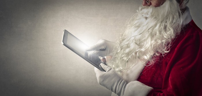 Santa Claus using a tablet.