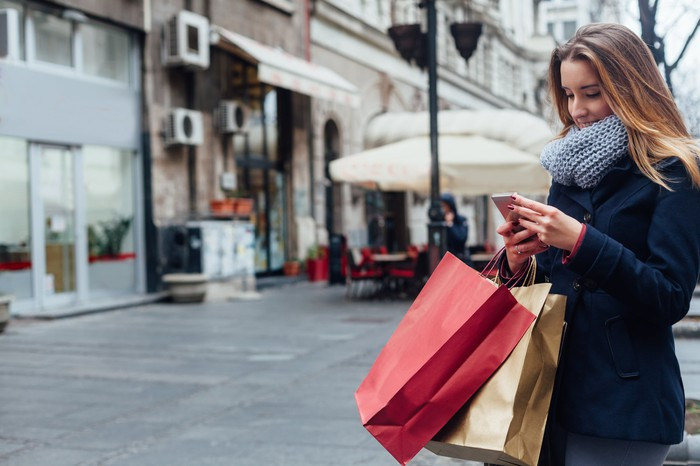 A woman looks at her phone while carrying shopping bags.