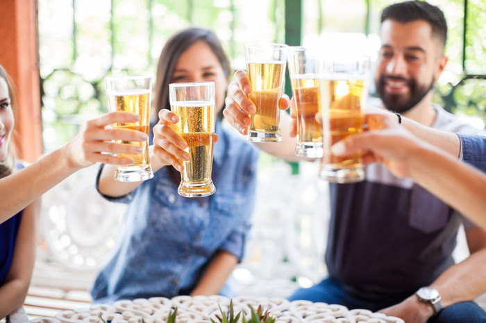 Group of friends toasting with glasses of beer.