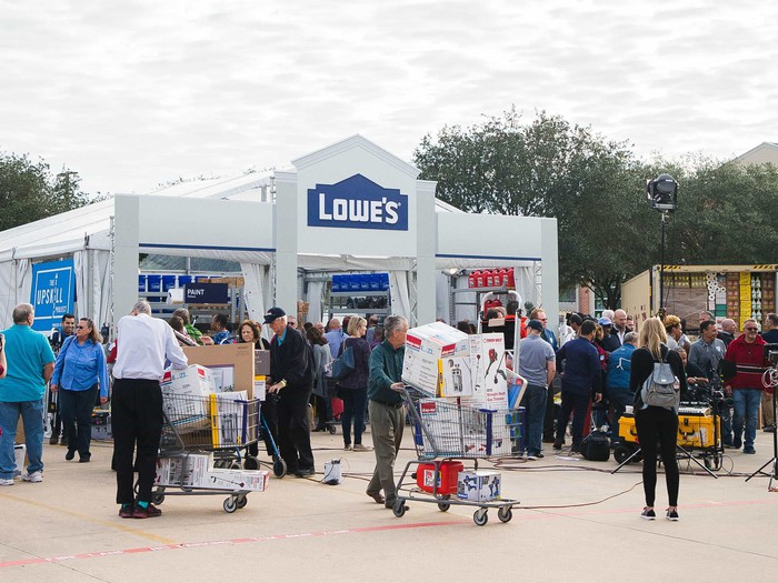 A crowd of people gather outside a Lowe's tent after Hurricane Harvey to pick up supplies and home goods.