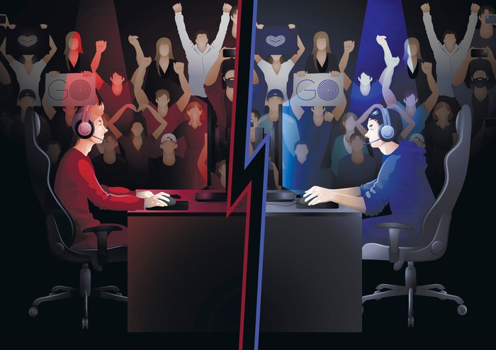 Two video gamers, one dressed in red and one in blue, sitting at desk facing each other with audiences for each side shown cheering in the background.