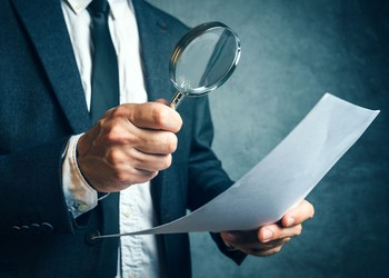 man inspecting document with magnifying glass tax inspector irs agent audit