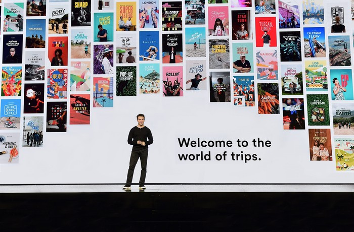 AirBnB chief executive Brian Chesky speaks onstage in front of a backdrop of different trips around the world