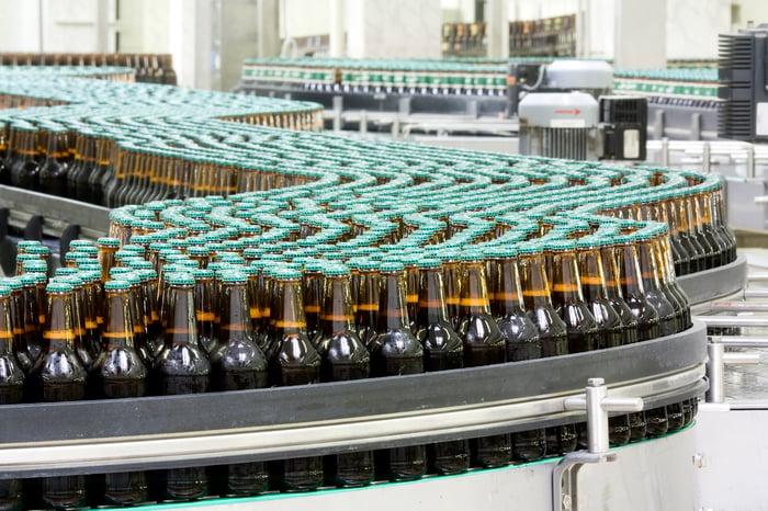 un-branded bottles on a conveyor belt in a bottling plant.