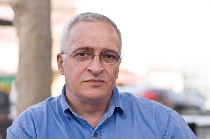 An older man with glasses and a blue button-down shirt sits outside with a serious expression.