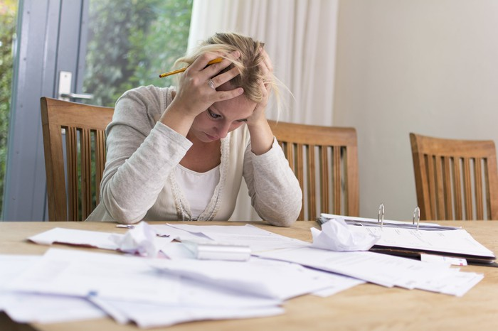 A woman holds her head in her hands, looking stressed as she pores over a pile of papers on a table.