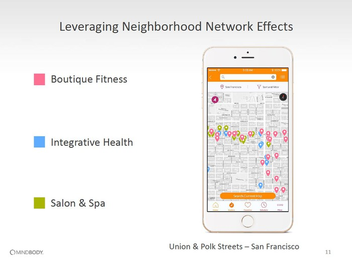 An Apple iPhone with a screen of a map with numerous boutique fitness, integrative health, and salon & spa locations clustered close together.