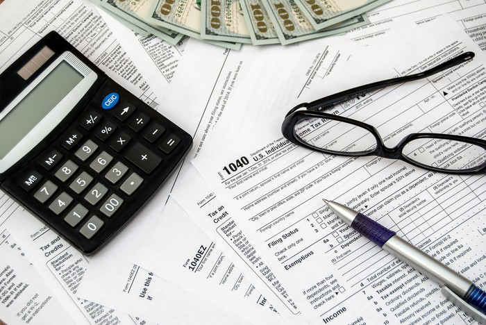 Tax forms with $100 bills, glasses, a pen, and a calculator.